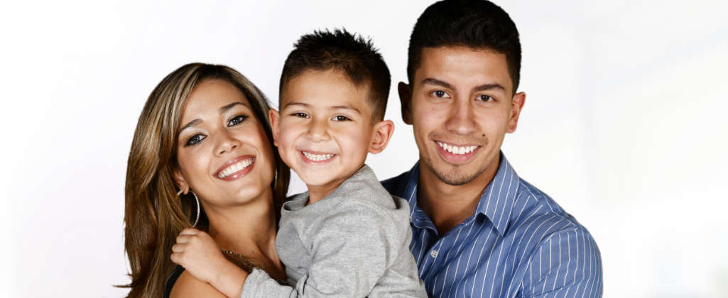 The Spanish family is smiling. Mom and dad are holding a child in their arms.