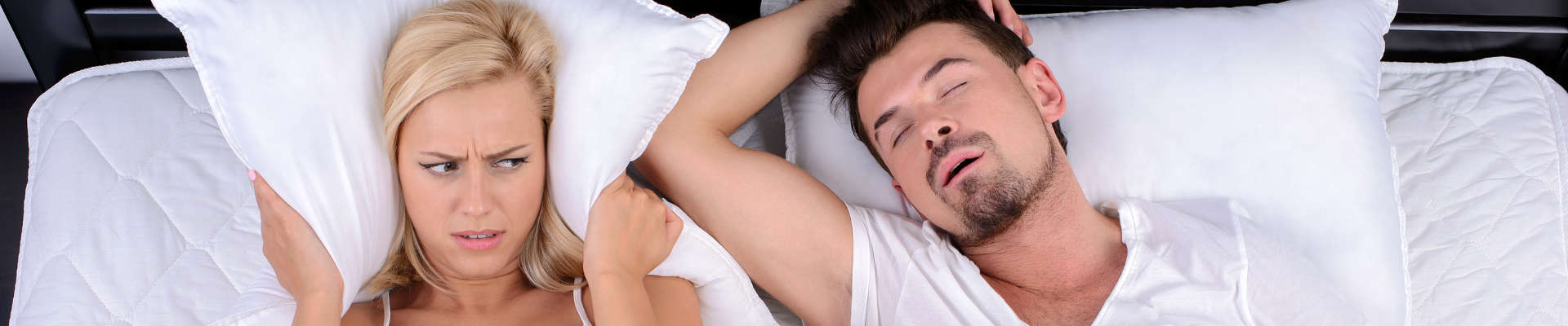 The man snores and the woman covers her head with a pillow. His snoring does not let her sleep.